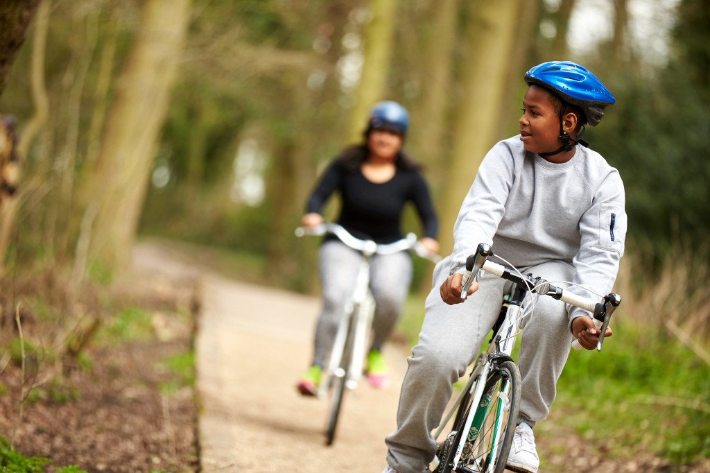 Teenage boy and Mum on bikes in the wood_World Obesity Federation